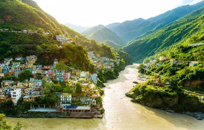 Confluence of two rivers Alaknanda and Bhagirathi give rise to the holy river of Ganga / Ganges at one of the five Prayags called Dev Prayag. Lush greenery in monsoons on the mountains. sunrise. India
